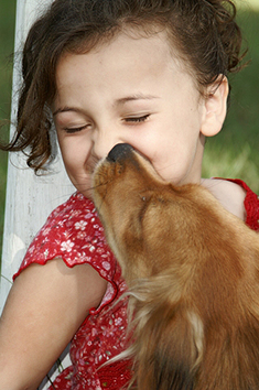 dog kissing girls face