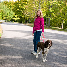 Girl walking dog on leash