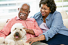 Couple spending time with dog on couch