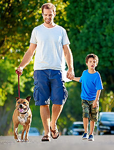 Father and son in taking dog for a walk on suburb street